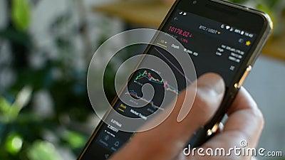 O empresário está verificando o gráfico de preços Bitmoney em troca criptográfica em tela de telefone celular amobile Preço futur filme