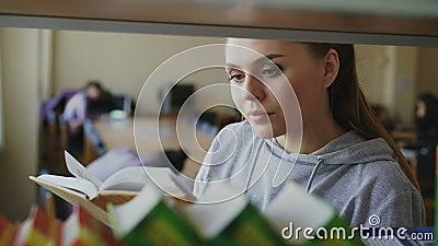 O estudante fêmea bonito caucasiano novo é prateleira próxima ereta com os livros na terra arrendada de biblioteca espaçoso grand vídeos de arquivo