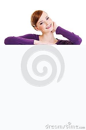 O femalel de sorriso está sobre uma placa da publicidade