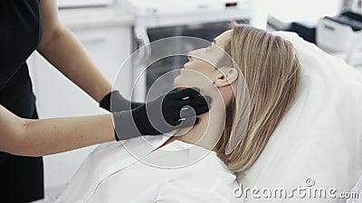 O fim acima das mãos do esteticista examina e toca na cara do paciente Mulher que fala com o cosmetologist antes do procedimento video estoque
