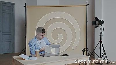 O fotógrafo profissional trabalha no App da edição da foto em seu computador pessoal Homem feliz que retoca imagens e relógio video estoque