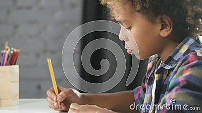 O garoto africano americano está sentado à mesa na sala de aula e fazendo dever de casa no caderno de educação video estoque