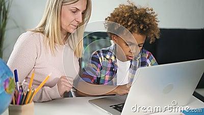 O garoto africano está sentado em sua mesa e procurando informações do novo laptop sem fio com tecnologia digital vídeos de arquivo