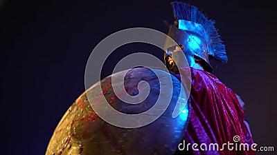 O gladiador romano na armadura de couro, no capacete e na capa de chuva vermelha é coberto com um protetor redondo e golpeia com  video estoque