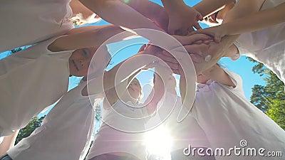 O grupo de crianças executa o cumprimento inspirador dos esportes com as mãos no campo de jogos do futebol da jarda no dia ensola video estoque