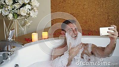 O homem alegre com espuma na barba está tomando o selfie usando o smartphone na banheira de hidromassagem no salão de beleza mode vídeos de arquivo