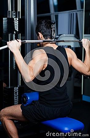 O homem atlético elabora no treinamento do gym