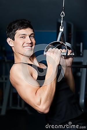 O homem atlético elabora no treinamento do gym da aptidão