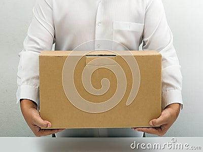 O homem carreg a caixa de papel marrom