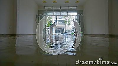 O homem da mulher cancela para fora a água do assoalho após o tufão devastador