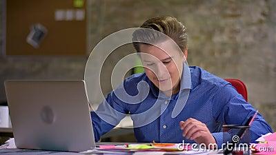 O homem de negócios louro de meia idade consegue a notícia e começos positivos girar em sua cadeira com mãos acima no escritório video estoque