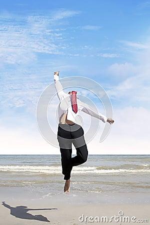 O homem de negócios que salta na praia