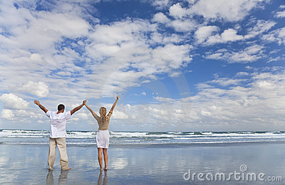 O homem e a mulher que comemoram os braços levantaram em uma praia