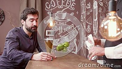 O homem em um contador da barra tenta uma cerveja e aprova o bom gosto vídeos de arquivo