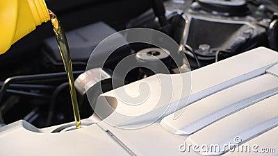 O homem está enchendo óleo de motor novo no motor Mecânico automático é trocar e derramar óleo fresco no motor vídeos de arquivo