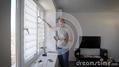 O homem está lendo uma instrução de instalação para cortinas em janelas e está olhando em detalhes, estando na sala de visitas de vídeos de arquivo