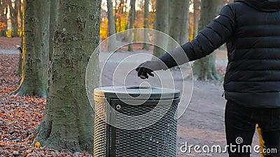 O homem joga o lixo em um escaninho de lixo em um parque filme