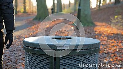 O homem joga o lixo em um escaninho de lixo em um parque video estoque