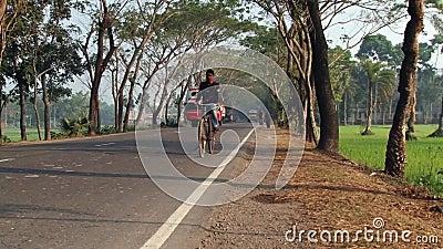 O homem monta a bicicleta pela estrada em Jessore, Bangladesh filme