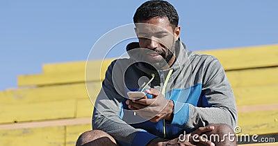 O homem negro novo no fato de esporte está datilografando uma mensagem em um telefone celular filme