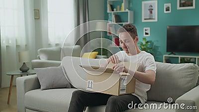 O homem novo entra em sua sala de visitas com pacote da caixa de cart?o, come?os que abrem o vídeos de arquivo