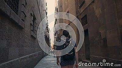O homem novo está andando apenas na rua estreita escura no quarto gótico em Barcelona filme