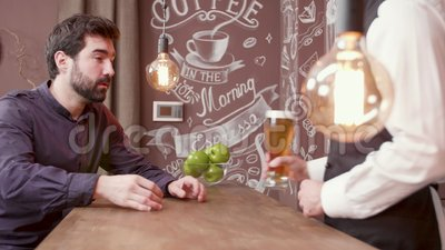 O homem novo que cumprimenta o barman e senta-se em um contador da barra filme