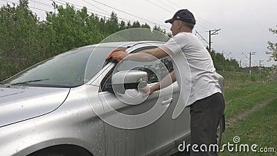 O homem p?e a cubeta sobre a terra e os come?os que lavam o autom?vel vídeos de arquivo