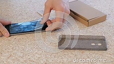 O homem repara o telefone Remove rachou o vidro protetor da tela do ` s do telefone filme