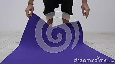 O homem rola a esteira separada da ioga no estúdio da aptidão Conceito da liberdade, da saúde e da ioga Feche acima do tiro slowm filme