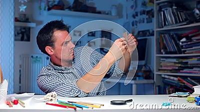 O homem sentado à mesa examina uma nota vídeos de arquivo
