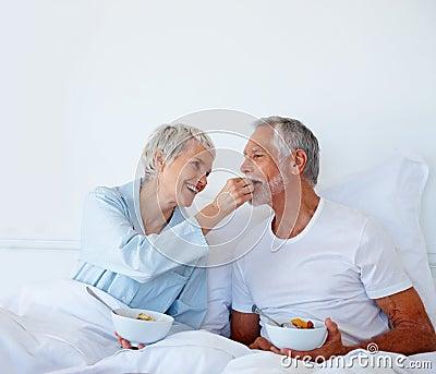 O homem sênior que é alimentação frutificar pela esposa quando na cama