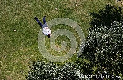 O homem toma sol em um parque em Londres central Imagem Editorial