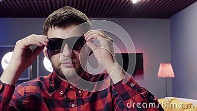 O indivíduo considerável decola óculos de sol e faz massagens suas orelhas na sala fornecida agradável filme