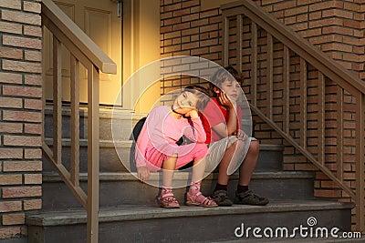 O irmão e a irmã sentam-se em escadas perto da porta