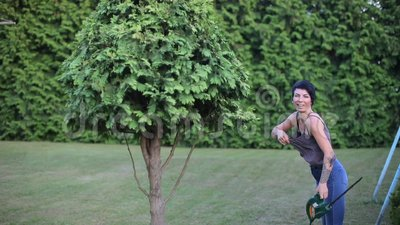 O jardineiro está aparando um arbusto alto filme