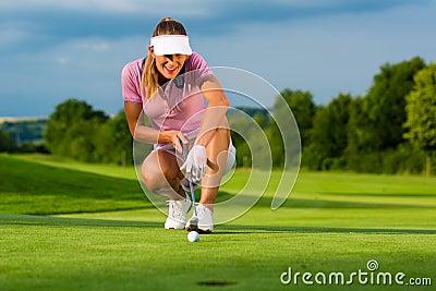 O jogador de golfe fêmea novo no curso que aponta para ela pôs