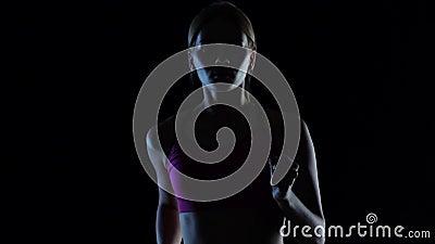 O jovem da menina na parte superior cor-de-rosa corre em um fundo preto Silhueta Movimento lento Fim acima vídeos de arquivo