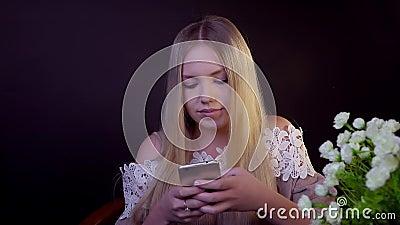 O louro novo está sorrindo em um fundo preto Imprime uma mensagem de texto no smartphone video estoque