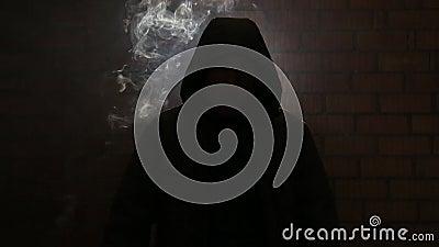 O maníaco fuma nervosamente esperando sua vítima em uma aleia escura filme