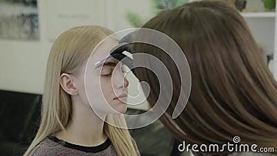O maquilhador faz a sobrancelha que mancha com as tinturas naturais, tonificando com hena, procedimentos cosméticos no salão de b vídeos de arquivo