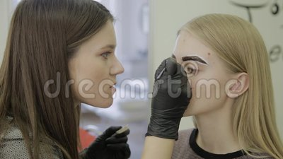 O maquilhador faz a sobrancelha que mancha com as tinturas naturais, tonificando com hena, procedimentos cosméticos no salão de b video estoque