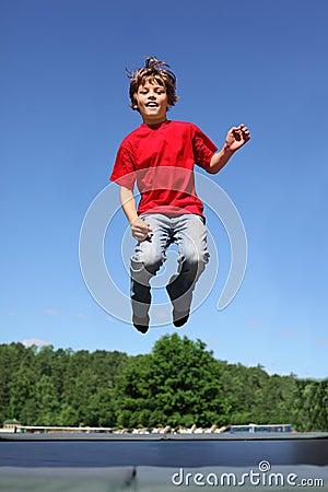 O menino alegre salta no trampoline
