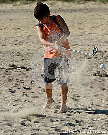 O menino bate uma esfera de golfe na praia
