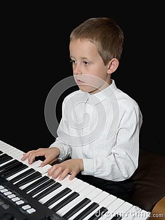 O menino joga o keyborad, piano, olhando na folha das notas