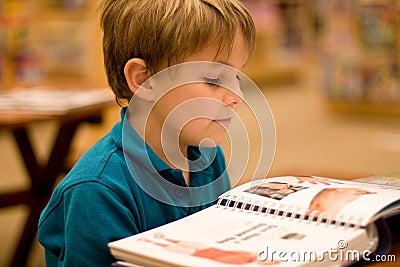 O menino lê um livro na biblioteca