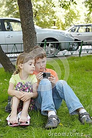 O menino olha a tela do telefone, irmã senta-se ao lado dele