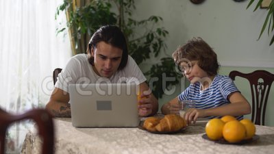O menino pequeno que eatting na mesa de cozinha e no cappuccino da bebida, a seguir dá alaranjado a seu irmão adulto Mais velho e video estoque