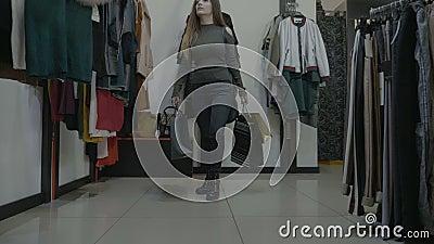 O modelo fêmea anda em uma loja com saltos altos e guarda seu telefone no bolso traseiro das calças de brim ao procurar a roupa n filme