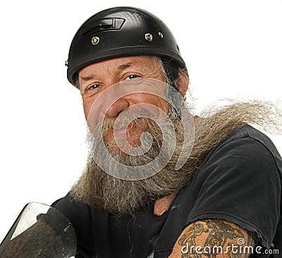 O motociclista sorri enquanto o vento funde através de sua barba